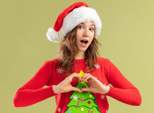 Jeune femme en pull de noël rouge et bonnet de noel faisant un geste cardiaque avec les doigts heureux et positif debout sur un mur vert