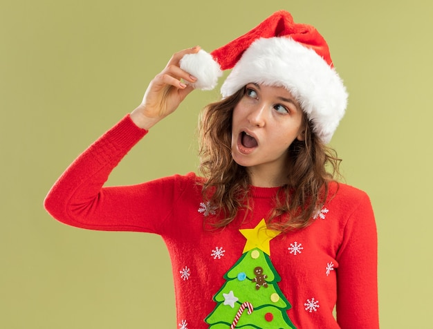 Jeune femme en pull de noël rouge et bonnet de noel regardant de côté surpris debout sur un mur vert