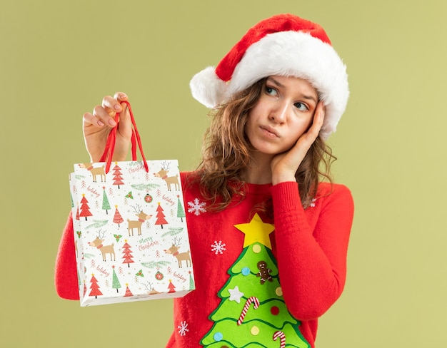 Jeune femme en pull de noël rouge et bonnet de noel tenant un sac en papier avec un cadeau de noël regardant de côté perplexe debout sur un mur vert