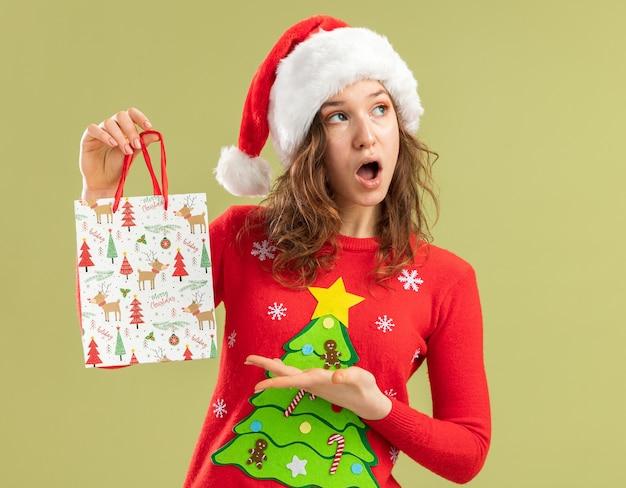 Jeune femme en pull de noël rouge et bonnet de noel tenant un sac en papier avec des cadeaux de noël se présentant avec le bras l'air surpris debout sur un mur vert