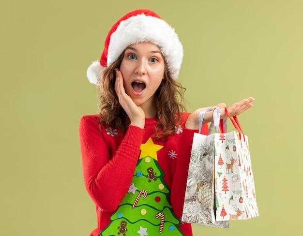 Jeune femme en pull de noël rouge et bonnet de noel tenant des sacs en papier avec des cadeaux de noël heureux et étonné debout sur un mur vert