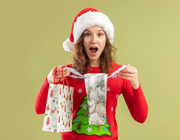 Jeune femme en pull de noël rouge et bonnet de noel tenant des sacs en papier avec des cadeaux de noël ouvrant des sacs étant heureuse et intriguée debout sur un mur vert