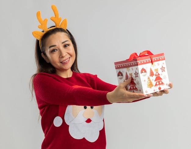 Jeune femme en pull de noël rouge portant une jante drôle avec des cornes de cerf tenant un cadeau de noël à sourire joyeusement heureux et positif