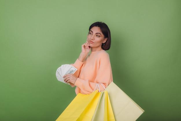 Jeune femme en pull pêche décontracté isolé sur mur d'olive verte tenant un ventilateur de billets de 100 dollars d'argent et de sacs à provisions pensant positif souriant copie espace