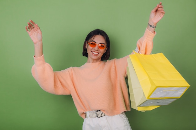 Jeune femme en pull pêche occasionnel isolé sur mur d'olive verte tenant des sacs à provisions élégant dans des verres orange sautant l'espace de copie drôle
