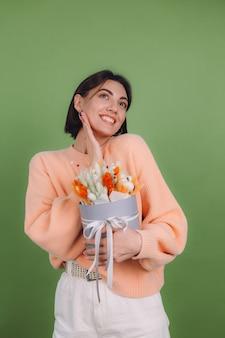 Jeune femme en pull pêche occasionnel isolé sur mur d'olive verte tenir la boîte à fleurs blanc orange composition de fleurs de coton gypsophile blé et lagurus pour un cadeau heureux étonné surpris