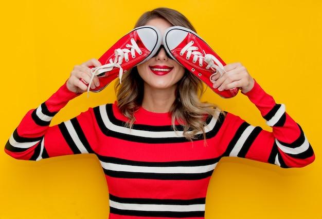 Jeune femme en pull rayé rouge avec gumshoes sur jaune