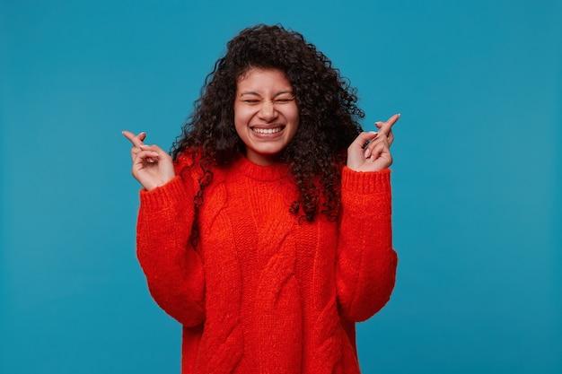 Jeune femme en pull rouge, garde les bras et les doigts croisés