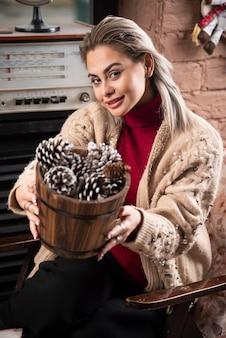 Jeune femme en pull rouge offrant un panier en bois plein de pommes de pin