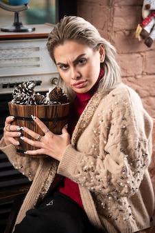 Jeune femme en pull rouge tenant un panier en bois plein de pommes de pin