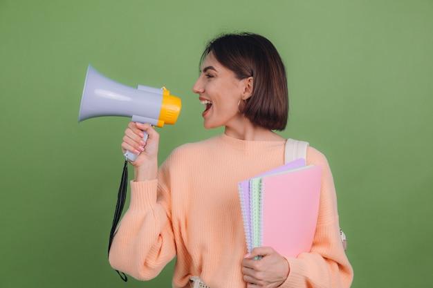 Jeune femme en pull et sac à dos pêche occasionnel isolé sur mur de couleur olive verte