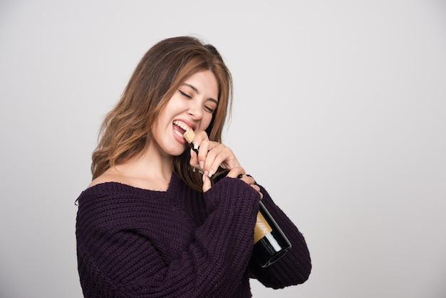 Jeune femme en pull tricoté chaud essayant d'ouvrir une bouteille de vin.