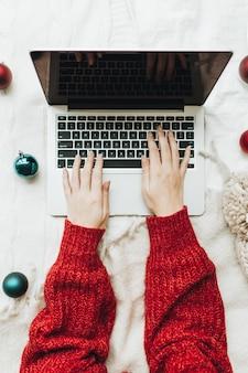 Jeune femme en pull tricoté rouge tapant sur ordinateur portable sur le lit blanc avec une couverture blanche décorée de boules rouges et bleues de noël