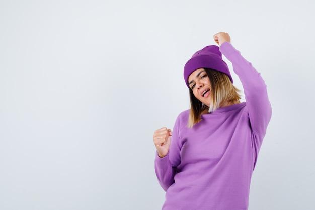 Jeune femme en pull violet, bonnet montrant le geste du gagnant et ayant l'air chanceux, vue de face.