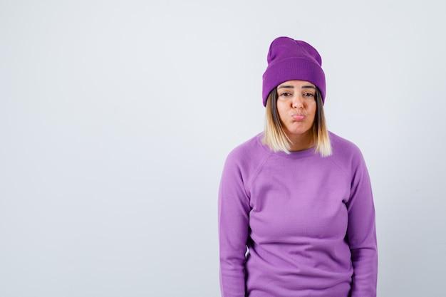 Jeune femme en pull violet, bonnet regardant la caméra tout en courbant les lèvres et l'air insatisfait, vue de face.