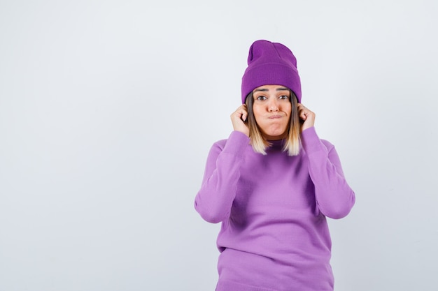 Jeune femme en pull violet, bonnet tirant vers le bas ses lobes d'oreilles tout en soufflant les joues et en ayant l'air drôle, vue de face.