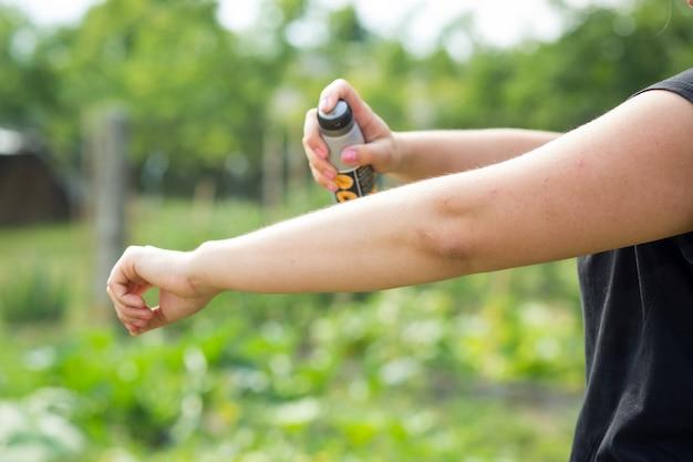 Jeune femme pulvérisant un insectifuge contre les moustiques dans la forêt