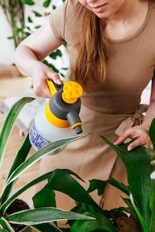Jeune femme pulvérisant les plantes avec un cadre vertical de l'eau recadrée image