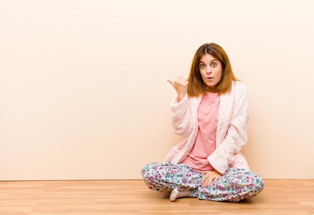 Jeune femme en pyjama assis à la maison, l'air étonné d'incrédulité, montrant un objet sur le côté et disant wow, incroyable