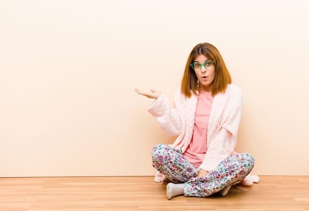 Jeune femme en pyjama assis à la maison, l'air surpris et choqué, la mâchoire tombée, tenant un objet avec une main ouverte sur le côté