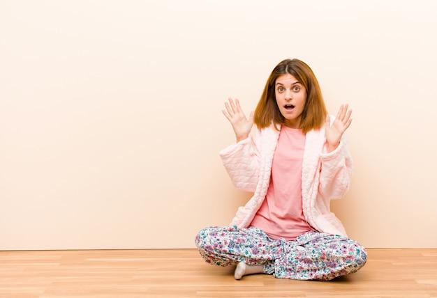 Jeune femme en pyjama assis à la maison, choquée et stupéfaite, la mâchoire tombée de surprise en réalisant quelque chose d'incroyable
