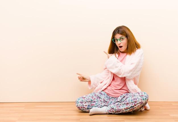 Jeune femme en pyjama assis à la maison, choquée et surprise, montrant du doigt la surface sur le côté avec un regard étonné et bouche bée
