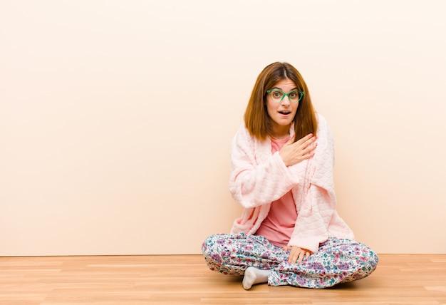 Jeune femme en pyjama assis à la maison, choquée et surprise, souriante, prenant la main à cœur, heureuse d'être la seule ou montrant de la gratitude