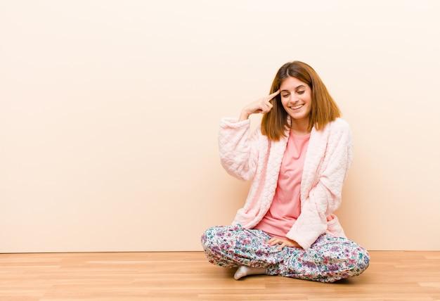 Jeune femme en pyjama assis à la maison, confuse et perplexe, montrant que vous êtes folle, folle ou perdue d'esprit