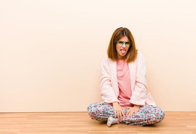 Jeune femme en pyjama assis à la maison, dégoûtée et irritée, tire la langue, n'aimant pas quelque chose de méchant et dégueulasse