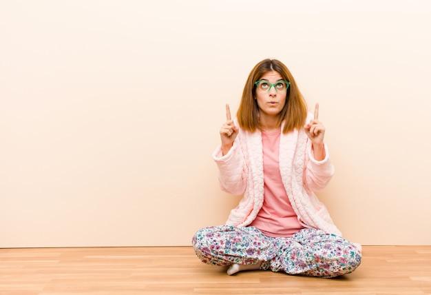 Jeune femme en pyjama assis à la maison, émerveillée et bouche bée dirigée vers le haut avec un regard choqué et surpris