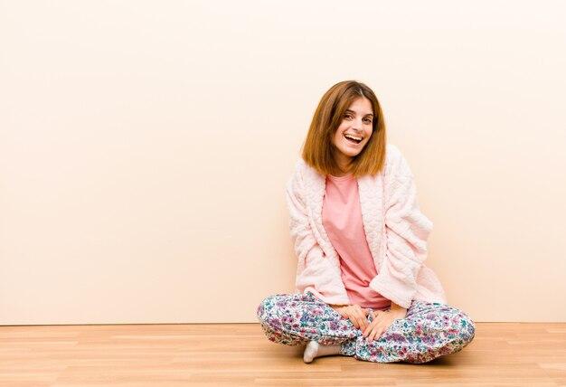 Jeune femme en pyjama assis à la maison avec un grand sourire amical et insouciant, l'air positif, détendu et heureux, glacée