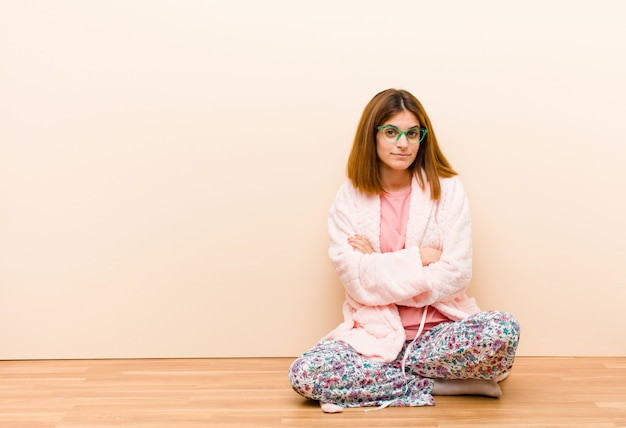 Jeune femme en pyjama assis à la maison, mécontente et déçue, sérieuse, ennuyée et en colère, bras croisés