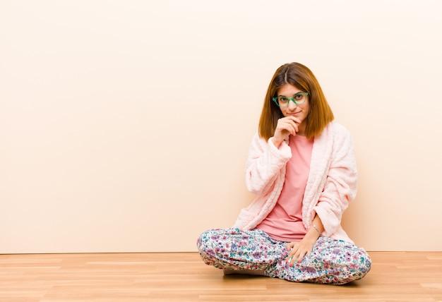 Jeune femme en pyjama assis à la maison à la recherche de sérieux