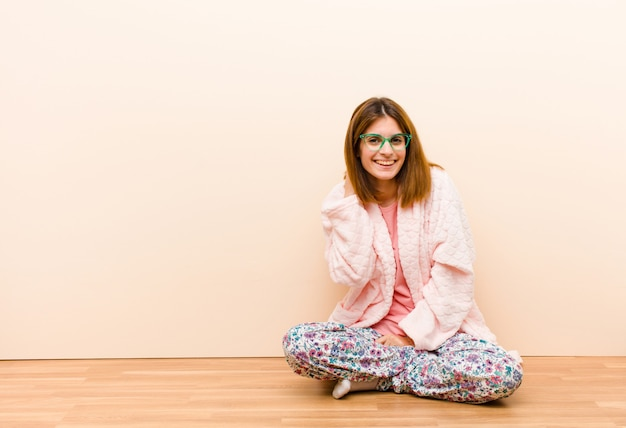 Jeune femme en pyjama assis à la maison en riant joyeusement et avec confiance avec un sourire désinvolte, heureux et amical