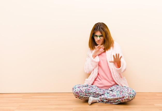Jeune femme en pyjama assis à la maison se sentant dégoûtée et nauséeuse s'éloignant de quelque chose de méchant malodorante ou puante disant beurk