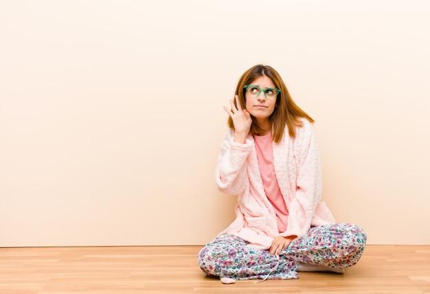 Jeune femme en pyjama assis à la maison, sérieuse et curieuse