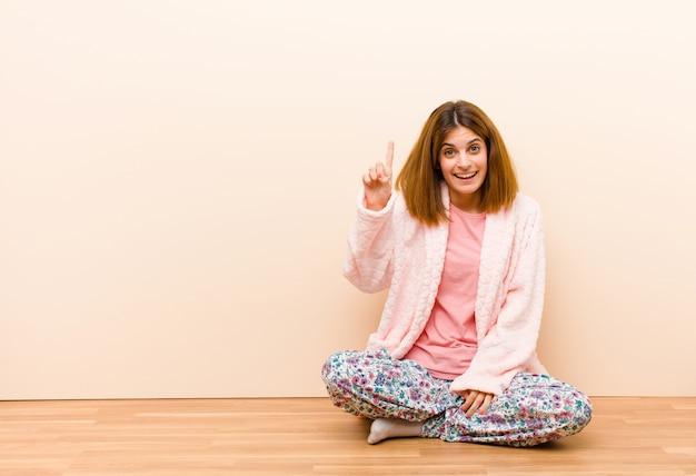 Jeune femme en pyjama assis à la maison, souriant joyeusement et avec bonheur, pointant vers le haut avec une main pour copier l'espace