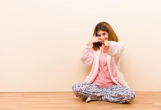 Jeune femme en pyjama assis à la maison souriant joyeusement et pointant vers la caméra tout en vous appelant plus tard geste, parler au téléphone