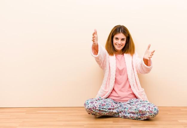 Jeune femme en pyjama assis à la maison souriant souriant donnant un câlin de bienvenue chaleureux, amical et affectueux, se sentant heureuse et adorable