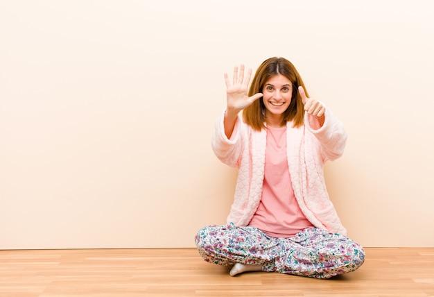 Jeune femme en pyjama assis à la maison, souriante et amicale, montrant le numéro six ou sixième avec la main en avant, comptant à rebours