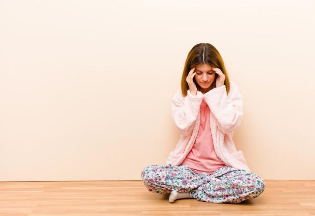 Jeune femme en pyjama assis à la maison, stressée et frustrée, travaillant sous pression, souffrant de maux de tête et troublée de problèmes