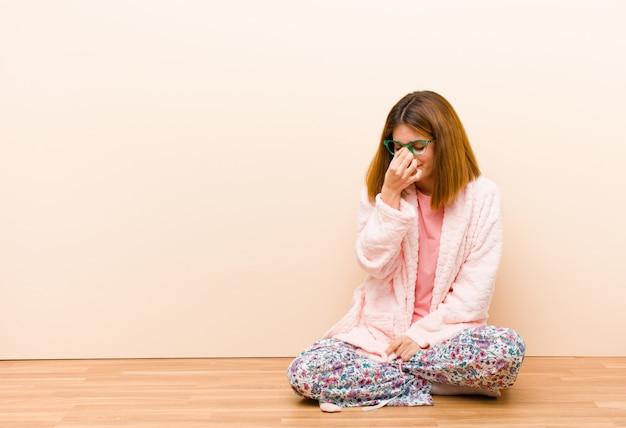 Jeune femme en pyjama assis à la maison, stressée, malheureuse et frustrée, touchant le front et souffrant de migraine, de maux de tête graves