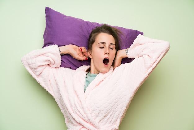 Jeune femme en pyjama bâillant