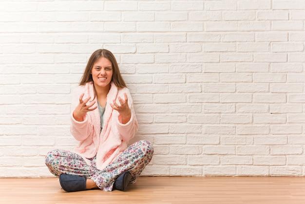 Jeune femme en pyjama en colère et contrariée