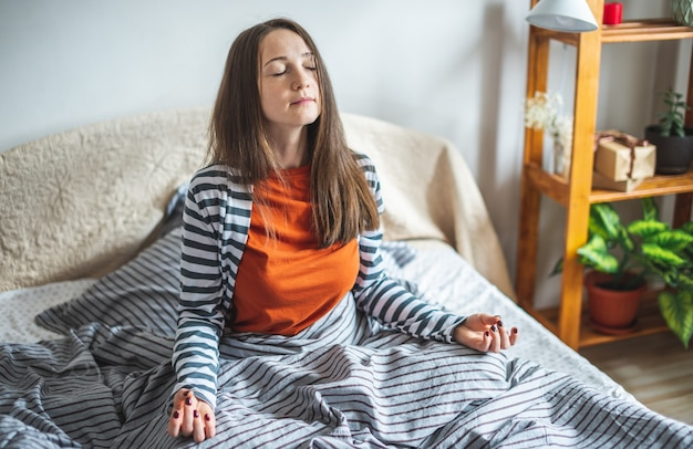 Une jeune femme en pyjama est assise sur le lit le matin en position du lotus et médite