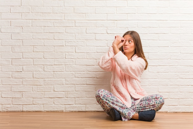 Jeune femme en pyjama faisant le geste d'une longue-vue