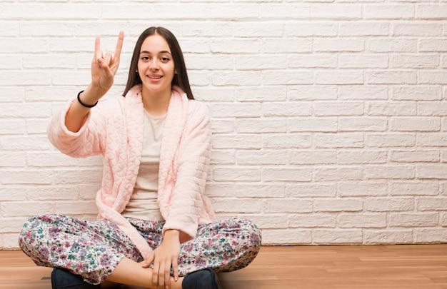 Jeune femme en pyjama faisant un geste rock