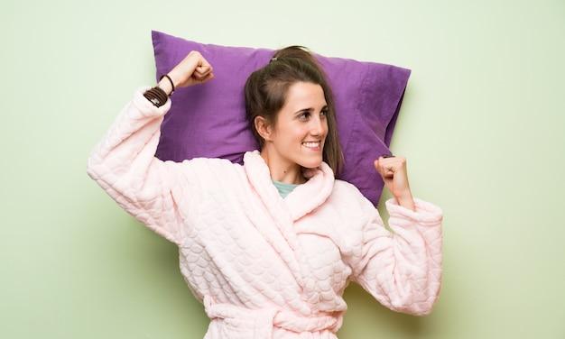 Jeune femme en pyjama faisant le geste de la victoire
