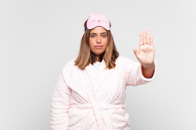 Jeune femme en pyjama, à la grave, sévère, mécontente et en colère montrant la paume ouverte faisant le geste d'arrêt