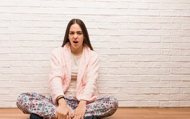 Jeune femme en pyjama hurlant très en colère et agressive